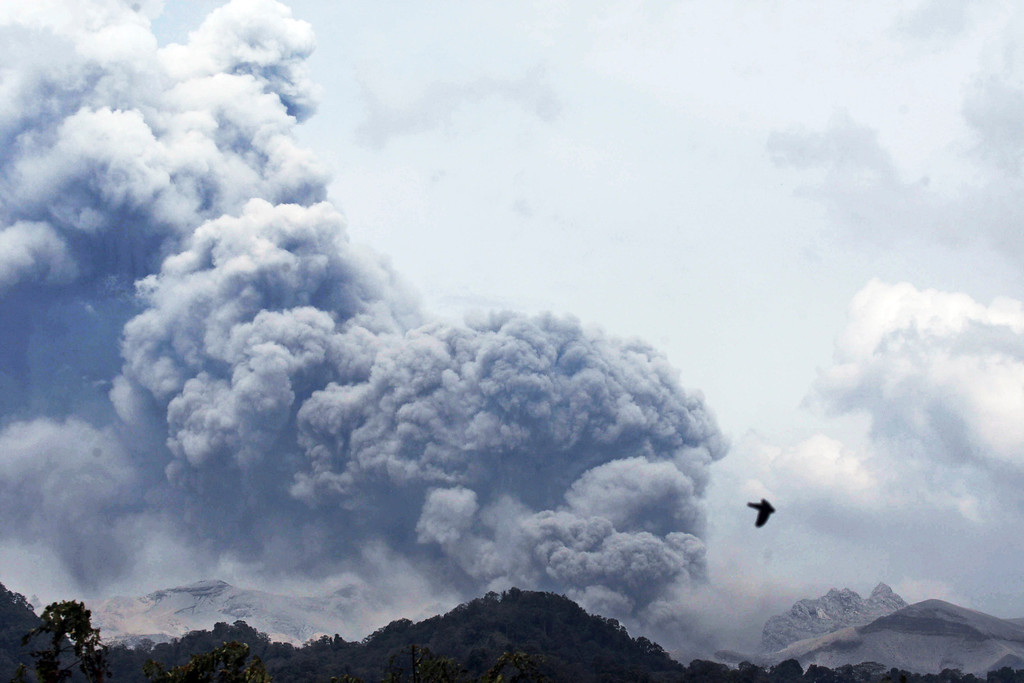 . Mount Kelud erupts, as seen from Anyar village in Blitar, East Java, Indonesia, Friday, Feb. 14, 2014. Volcanic ash from the major eruption in Indonesia shrouded a large swath of the country\'s most densely populated island on Friday, closed three international airports and sent thousands fleeing. (AP Photo/Trisnadi)