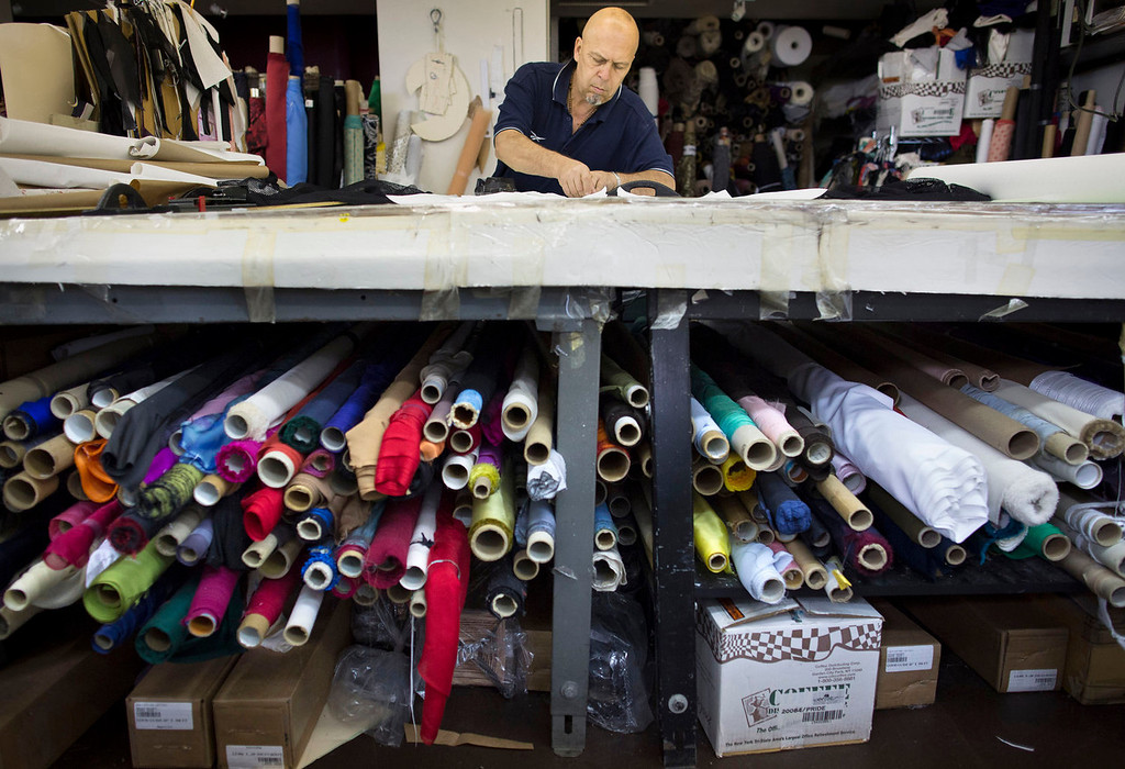 . Fabric cutter Oscar Santa works on a table stacked with rolls of fabric in the New York studio of fashion designer Carmen Marc Valvo. Valvo will show his Spring 2014 show on Sept. 6 at Lincoln Center in New York. (AP Photo/John Minchillo)