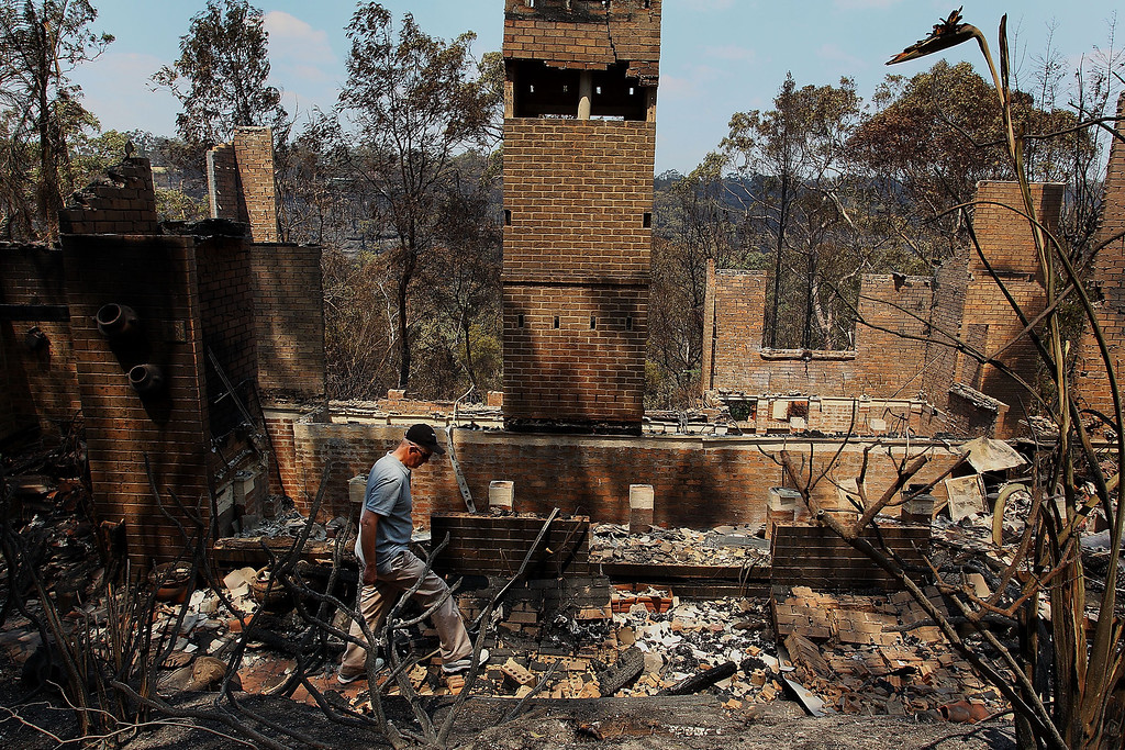 . Noel Willis inspects his home destroyed by fire on October 18, 2013 in Winmalee, Australia.  (Photo by Lisa Maree Williams/Getty Images)