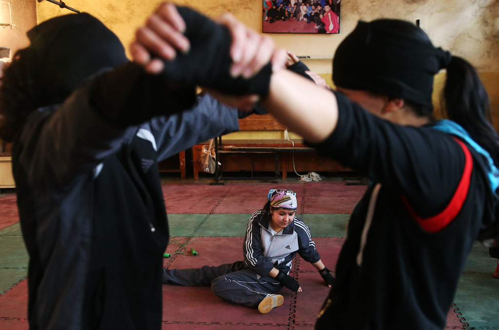 . In this Wednesday, March, 5, 2014 photo, Afghan female boxers exercise during a practice session at the Kabul Stadium boxing club, Afghanistan. The women, who are 18 and older, donít have much more than determination, and a trainer who runs them through their paces, watches as they spar, corrects their technique, tells them when to jab, how to protect themselves, when to power through with a left and then a right. (AP Photo/Massoud Hossaini)
