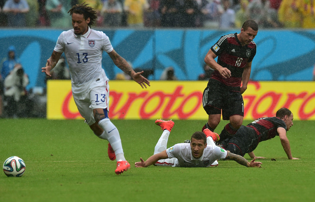 . US midfielder Jermaine Jones (L) and US defender Fabian Johnson (2nd L) vie for the ball with Germany\'s forward Lukas Podolski (2nd R) and Germany\'s defender Benedikt Hoewedes (R) during a Group G football match between US and Germany at the Pernambuco Arena in Recife during the 2014 FIFA World Cup on June 26, 2014. AFP PHOTO / NELSON  ALMEIDA/AFP/Getty Images