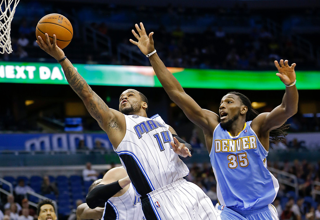 . Orlando Magic\'s Jameer Nelson (14) gets past Denver Nuggets\'s Kenneth Faried (35) for a lay up during the second half of an NBA basketball game in Orlando, Fla., Wednesday, March 12, 2014. Denver won 120-112. (AP Photo/John Raoux)