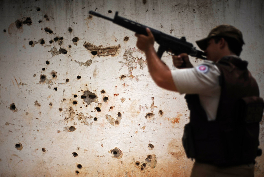 ". Police patrol past the ""rifle wall\"" pockmarked by bullets from many shootouts between drug gangs and police, in the Nordeste de Amaralina slum complex in Salvador, Bahia State, March 28, 2013. One of Brazil\'s main tourist destinations and a 2014 World Cup host city, Salvador suffers from an unprecedented wave of violence with an increase of over 250% in the murder rate, according to the Brazilian Center for Latin American Studies (CEBELA). Picture taken March 28, 2013.  REUTERS/Lunae Parracho"