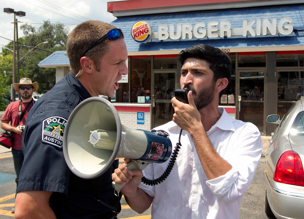 . A police officer orders Greg Casar, of the Workers Defense Project, to get off the property of a Burger King in Austin, Texas, on Thursday Aug. 29, 2013. Casar was leading a group of about 200 people who support the fast food strike in a march along Guadalupe Street.  (AP Photo/Austin American-Statesman, Jay Janner)