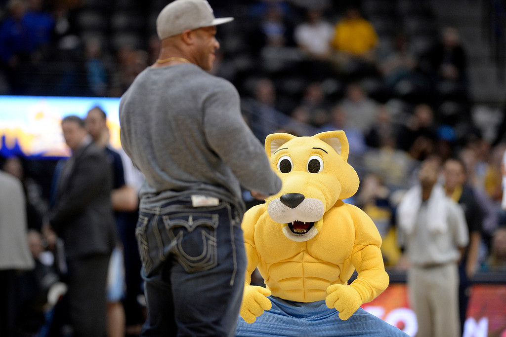 """. Denver Nuggets mascot Rocky bears his physique in front of Mr. Olympia competitor Phil \""""The Gift\"""" heat as they compete to make no-look half court baskets during the fourth quarter of the Grizzlies\' 94-92 win. (Photo by AAron Ontiveroz/The Denver Post)"""