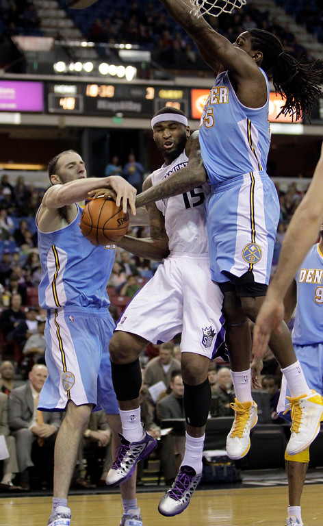 . Sacramento Kings center DeMarcus Cousins, center, is fouled by Denver Nuggets center Kosta Koufos, left,as Nuggets forward Kenneth Faried defends during the third quarter of an NBA basketball game in Sacramento, Calif., Sunday, Dec. 16, 2012.  The Nuggets won 122-97.(AP Photo/Rich Pedroncelli)