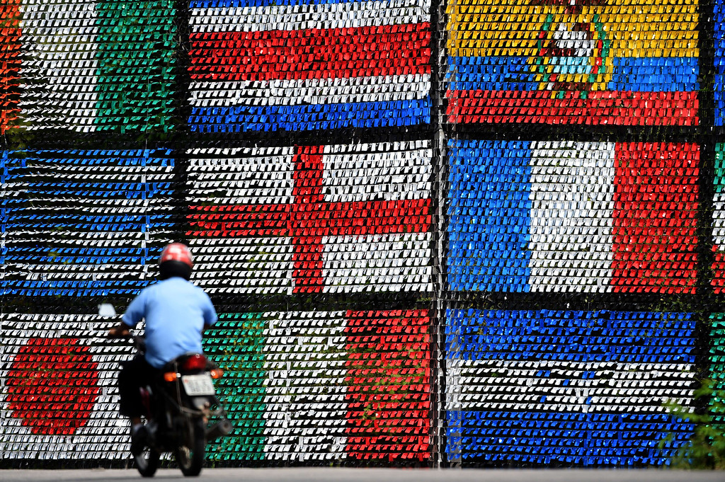 . A motorcyclist rides past a wall of flags on a road in Porto Seguro, on June 18, 2014, during the 2014 FIFA World Cup. PATRIK STOLLARZ/AFP/Getty Images