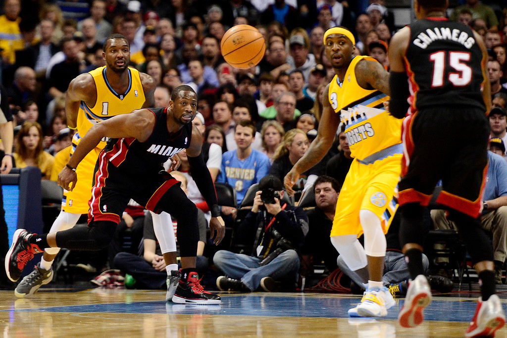 . Dwyane Wade (3) of the Miami Heat passes to Mario Chalmers (15) as Jordan Hamilton (1) of the Denver Nuggets and Ty Lawson (3) defend during the first half of action.   (Photo by AAron Ontiveroz/The Denver Post)