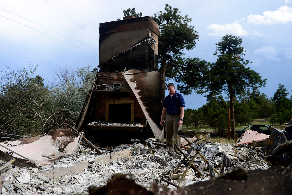 . Jesse Russow surveys the damage of his rental property, which was the southernmost home burned on the west side of Vollmer Road, June 18, 2013.   (Photo by AAron Ontiveroz/The Denver Post)