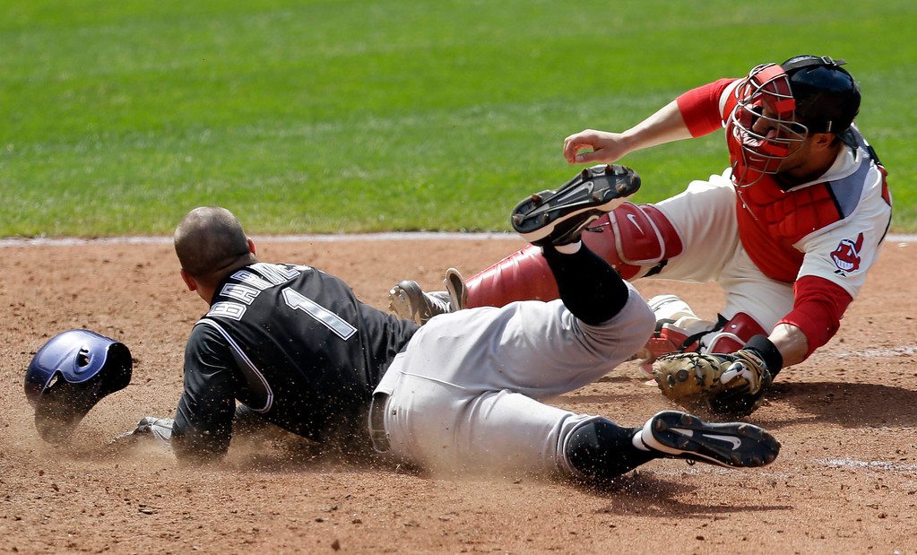 . Colorado Rockies\' Brandon Barnes, left, scores ahead of the tag by Cleveland Indians catcher George Kottaras in the seventh inning of a baseball game on Sunday, June 1, 2014, in Cleveland. Barnes scored on a sacrifice fly hit by Charlie Blackmon. (AP Photo/Tony Dejak)