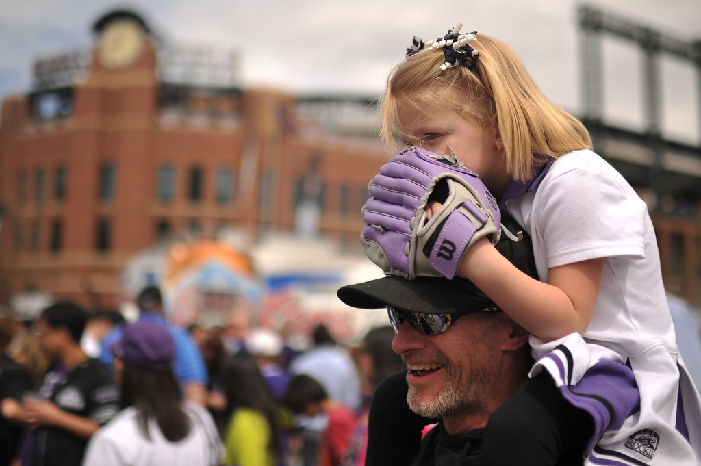. Lizzie George, 4, and her father Mac George from Longmont check out the events outside Coors Field. The Colorado Rockies took on the San Diego Padres on Opening Day at Coors Field in Denver, Colorado. (Photo by Hyoung Chang/The Denver Post)
