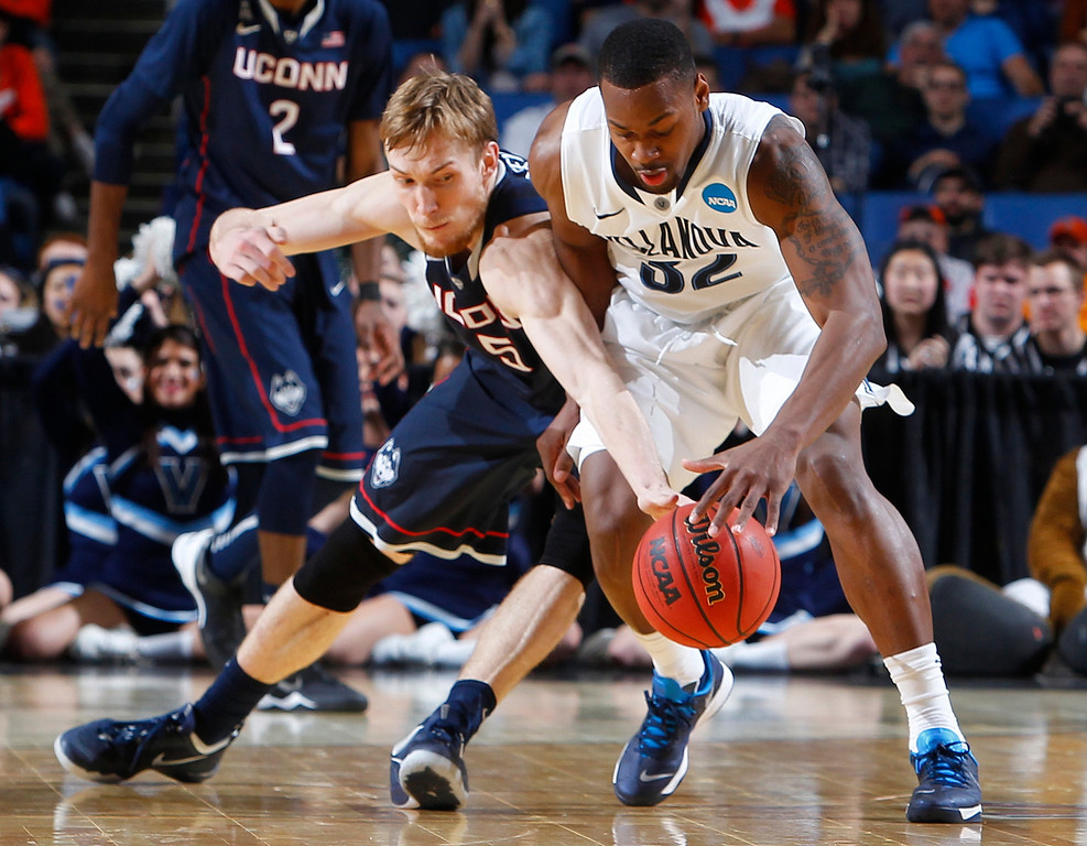 . Connecticut\'s Niels Giffey (5) and Villanova\'s James Bell (32) reach for the loose ball during the second half of a third-round game in the NCAA men\'s college basketball tournament in Buffalo, N.Y., Saturday, March 22, 2014. (AP Photo/Bill Wippert)