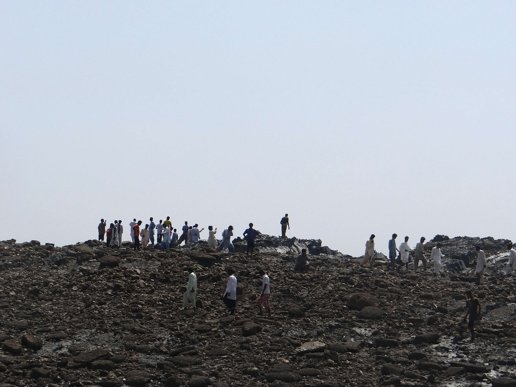. In this photo released by the Pakistani Government, Pakistani men walk on an island that appeared 2 kilometres off the coastline of Gwadar on September 25, 2013, after an earthquake the day before. The National Institute of Oceanography has sent a team to survey the island, which stands about 20 metres (70 feet) high. Pakistani rescuers strived to reach victims of a huge earthquake that killed more than 230 people and toppled thousands of mud-built homes when it hit the country\'s southwest with enough force to create a new island off the coast. AFP PHOTO/ Pakistan Government