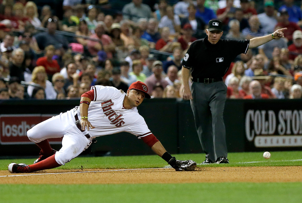 . Arizona Diamondbacks\' Martin Prado, left, mis-plays a ball hit by Colorado Rockies\' Michael Cuddyer during the fourth inning of a baseball game, Thursday, April 25, 2013, in Phoenix. (AP Photo/Matt York)