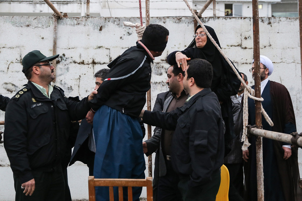 . The mother (R) of Abdolah Hosseinzadeh, who was murdered in 2007, slaps Balal who killed her son during the execution ceremony in the northern city of Nowshahr on April 15, 2014 just before she removed the noose around his neck with the help of her husband, sparing the life of her son\'s convicted murderer. AFP PHOTO/ARASH KHAMOOSHI/AFP/Getty Images