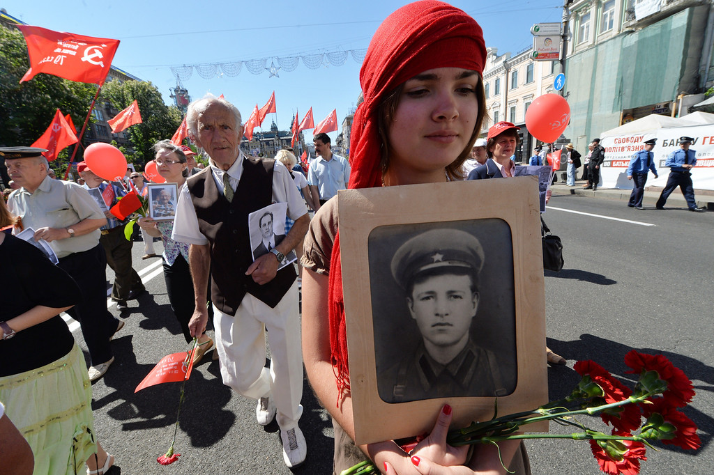 . A girl carries the picture of a died relative during a Victory Day march in the center of Kiev on May 9, 2013. Ukraine, Russia and other Soviet Union countries today celebrate the victory over Nazi Germany in World War II. SERGEI SUPINSKY/AFP/Getty Images