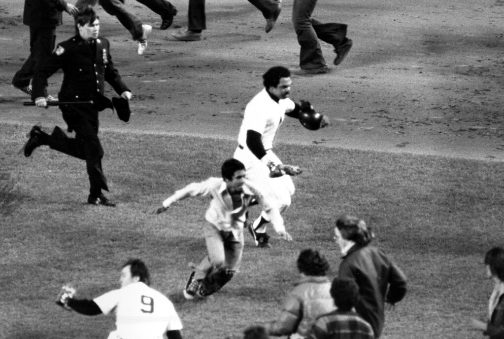 . New York Yankees slugger Reggie Jackson, center, makes a run for the dugout after the final out and the Yankees\' win of the World Series title, New York, October 18, 1977. Jackson led his team to an 8-4 victory by hitting three home runs in game six of the championship. (AP Photo)