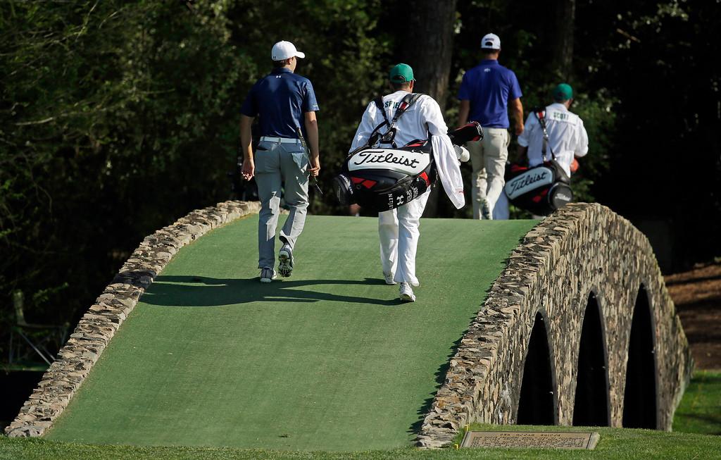 . Jordan Spieth, left, follows Adam Scott, of Australia, across the Hogan Bridge with their caddies during the third round of the Masters golf tournament Saturday, April 12, 2014, in Augusta, Ga. (AP Photo/Darron Cummings)