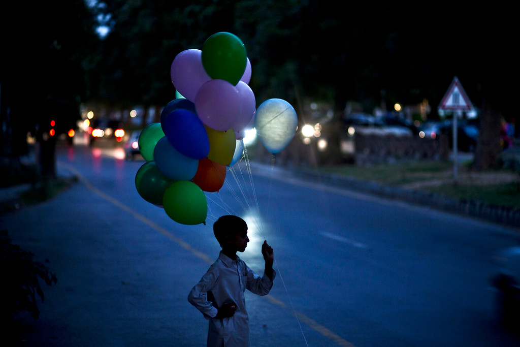 """. Pakistani student, Qammar Nawaz, 11, who helps his father in selling balloons, stands on a roadside waiting for customers during the Muslim holiday of Eid al-Adha, or \""""Feast of Sacrifice\"""", in Islamabad, Pakistan, Thursday, Oct. 17, 2013. (AP Photo/Muhammed Muheisen)"""