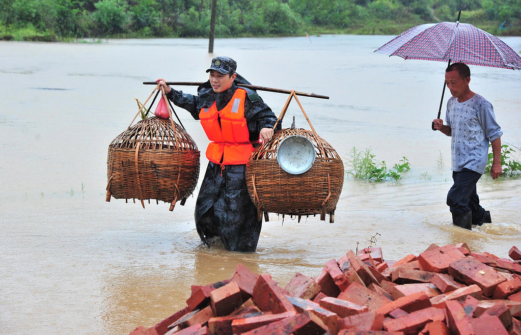 . A rescue worker (L) helping to relocate belongings of flood victims in Dao county of Yongzhou, central China\'s Hunan province on August 18, 2013. Devastating floods at opposite ends of China have left at least 74 people dead and forced hundreds of thousands to evacuate their homes in recent days, officials and state media said on August 19.   AFP PHOTOAFP/AFP/Getty Images