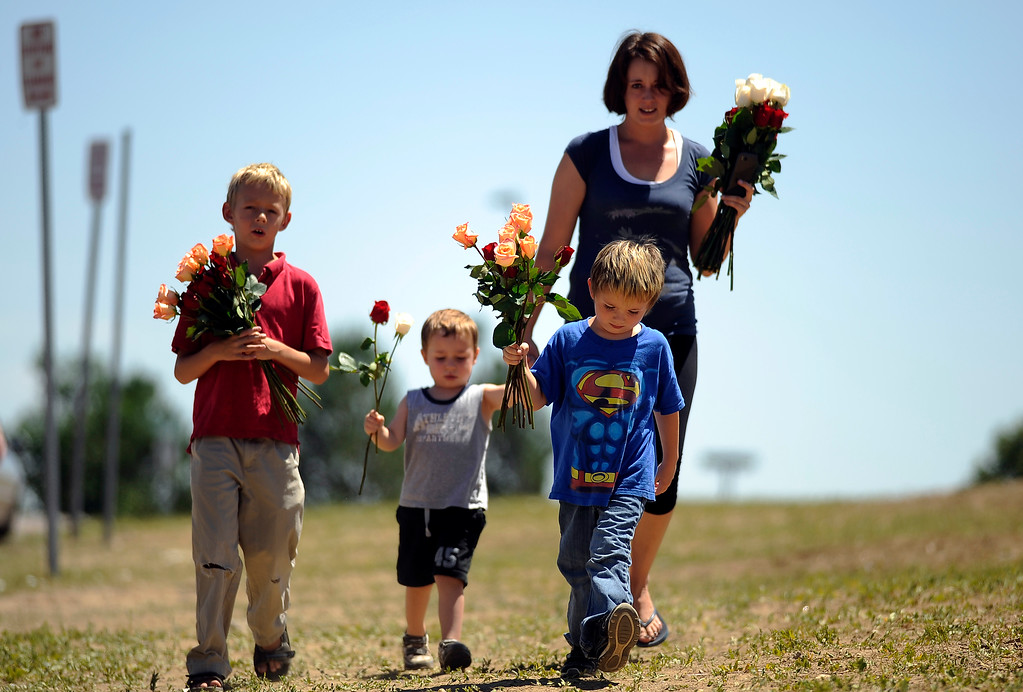 . Families head to the memorial for shooting victims at the corner of E. Centerpoint Dr. and S. Sable Blvd. in Aurora, Colo. on Saturday, July 21, 2012. From left, Caleb Ammon, 9, Devon Fallis, 3, Blake Fallis, 5, and their mother Lyndsey Ammon of Aurora. Hyoung Chang, The Denver Post