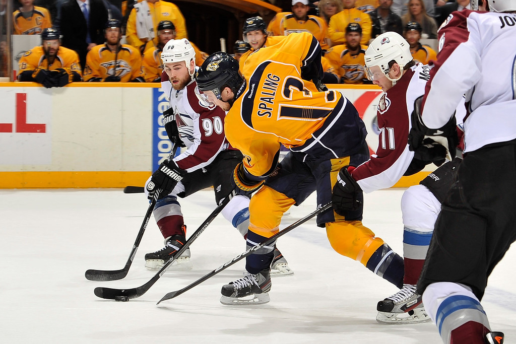 . NASHVILLE, TN - JANUARY 18:  Nick Spaling #13 of the Nashville Predators carries the puck between Ryan O\'Reilly #90 and Jamie McGinn #11 of the Colorado Avalanche at Bridgestone Arena on January 18, 2014 in Nashville, Tennessee.  (Photo by Frederick Breedon/Getty Images)