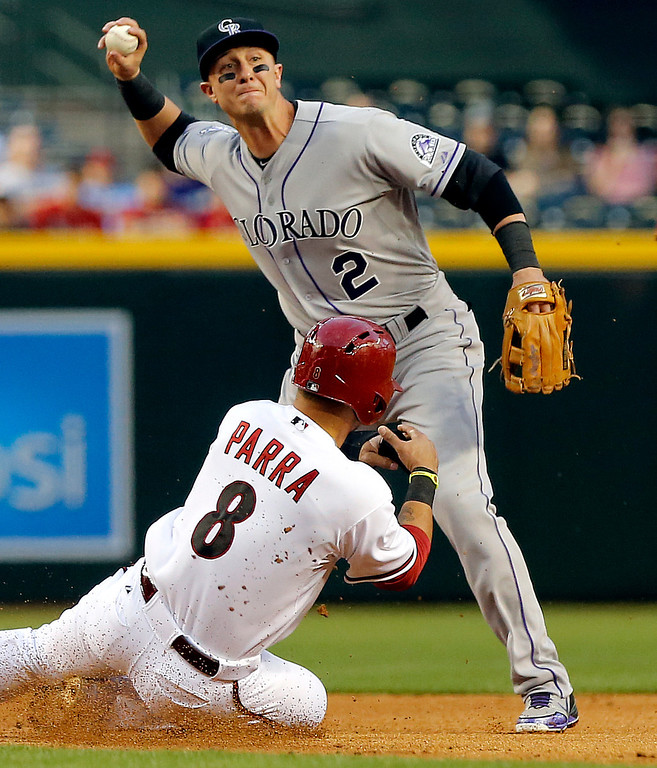 . Colorado Rockies\' Troy Tulowitzki (2) forces out Arizona Diamondbacks\' Gerardo Para (8) as he turns a double play on Diamondbacks\' Martin Prado during the first inning of a baseball game, Thursday, April 25, 2013, in Phoenix. (AP Photo/Matt York)