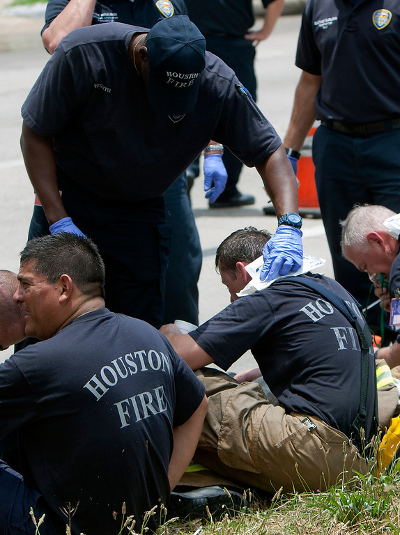 . A firefighter tends to colleagues sitting on the ground during blaze at the Southwest Inn on U.S. 59 in Houston on Friday, May 31, 2013. (AP Photo/Houston Chronicle, Cody Duty)