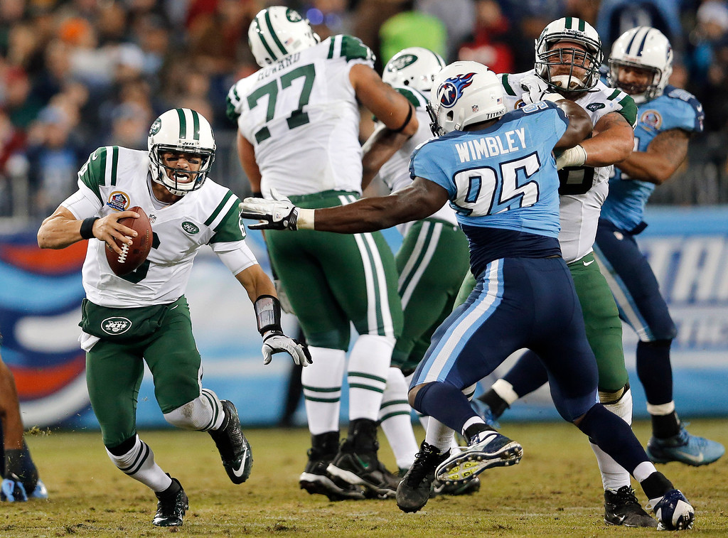. New York Jets quarterback Mark Sanchez (6) scrambles away from Tennessee Titans defensive end Kamerion Wimbley (95) in the second quarter of an NFL football game, Monday, Dec. 17, 2012, in Nashville, Tenn. (AP Photo/Joe Howell)
