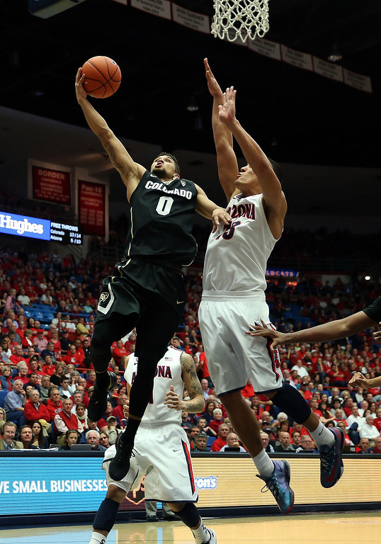 . Askia Booker #0 of the Colorado Buffaloes lays up a shot past Nick Johnson #13 of the Arizona Wildcats during the second half of the college basketball game at McKale Center on January 23, 2014 in Tucson, Arizona. The Wildcats defeated the Buffaloes 69-57.  (Photo by Christian Petersen/Getty Images)