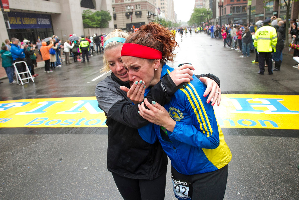 """. Erin Roy (L) comforts Elise Wulff as runners cross the finish line after completing the final mile of the Boston Marathon course during \""""#onerun\"""" in Boston, Massachusetts, May 25, 2013. Wulff participated in the marathon but was unable to finish when the course was shut down following the bombing attack.    REUTERS/Dominick Reuter"""