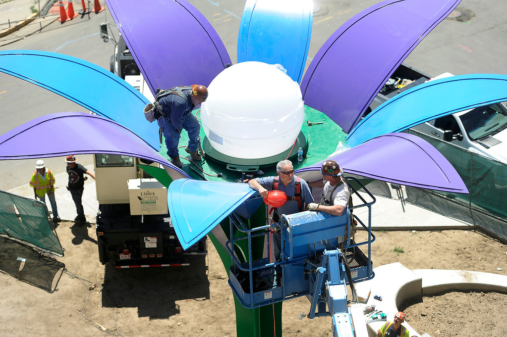 . Iron workers Brad Weaver, left, and Rex Stacy, right, from Peak Custom Fabrication, bring artist Emanuel Martinez up to see the white bulb in place on a 30 foot-tall, 10-ton metal sculpture of a large flower titled Flor De La Alma. June 25, 2013. A crane was used to lift the bulb and place it gently on the three story-high stem, which will glow at night. The flower sculpture sits in the courtyard of new apartment buildings under construction at the Housing Authority of the City and County of Denver at West 10th Avenue and Navajo Street. (Photo By Kathryn Scott Osler/The Denver Post)