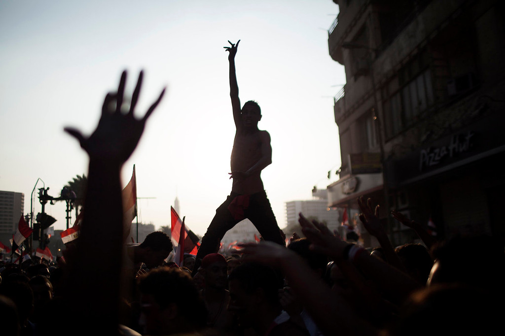 """. Egyptian protesters chant slogans against Egyptian Islamist President Mohammed Morsi in Tahrir Square in Cairo, Wednesday, July 3, 2013. A statement on the Egyptian president\'s office\'s Twitter account has quoted Mohammed Morsi as calling military measures \""""a full coup.\"""" The denouncement was posted shortly after the Egyptian military announced it was ousting Morsi, who was Egypt\'s first freely elected leader but drew ire with his Islamist leanings. The military says it has replaced him with the chief justice of the Supreme constitutional Court, called for early presidential election and suspended the Islamist-backed constitution. (AP Photo/ Manu Brabo)"""