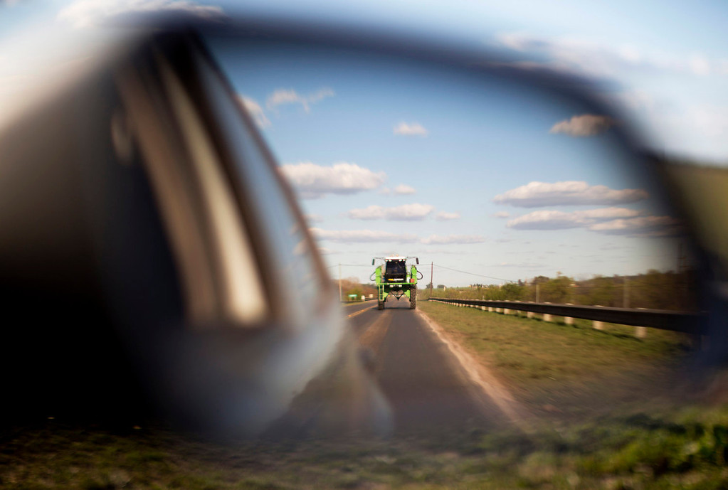 """. A tractor used for spraying agrochemicals is reflected in a car\'s side view mirror on a road in Parana, in Entre Rios province, Argentina on Sept. 24, 2013. Glyphosate represents two-thirds of all agrochemicals used in Argentina, but resistance to pesticides is forcing farmers to mix in other poisons such as 2,4,D, which the U.S. military used in \""""Agent Orange\"""" to defoliate jungles during the Vietnam War. (AP Photo/Natcha Pisarenko)"""