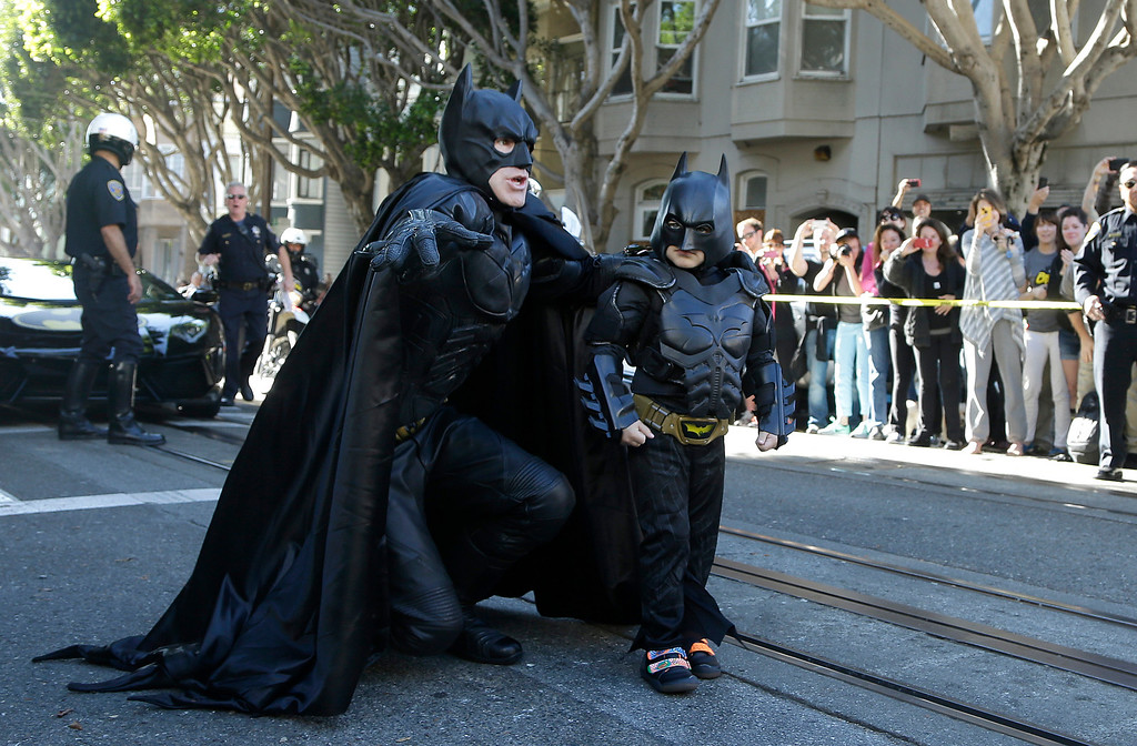 """. Miles Scott, dressed as Batkid, right, walks with Batman before saving a damsel in distress in San Francisco, Friday, Nov. 15, 2013.  San Francisco turned into Gotham City on Friday, as city officials helped fulfill Scott\'s wish to be \""""Batkid.\"""" Scott, a leukemia patient from Tulelake in far Northern California, was called into service on Friday morning by San Francisco Police Chief Greg Suhr to help fight crime, The Greater Bay Area Make-A-Wish Foundation says. (AP Photo/Jeff Chiu)"""