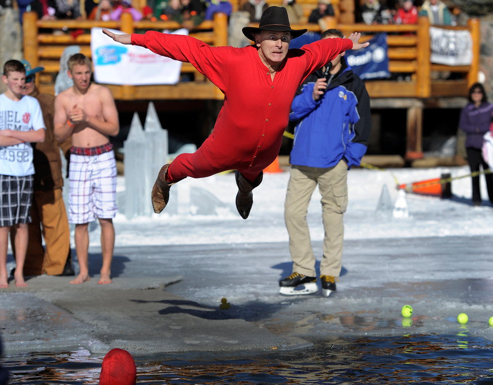 . Dozens joined in for the 6th annual Evergreen Lake Plunge on New Years Day, 2013, where only the very brave jumped, dove, and even performed a belly flop into the icy waters of Evergreen Lake. Keeping on his cowboy boots and hat, John Sawyer from Denver performs a belly flop. Kathryn Scott Osler, The Denver Post