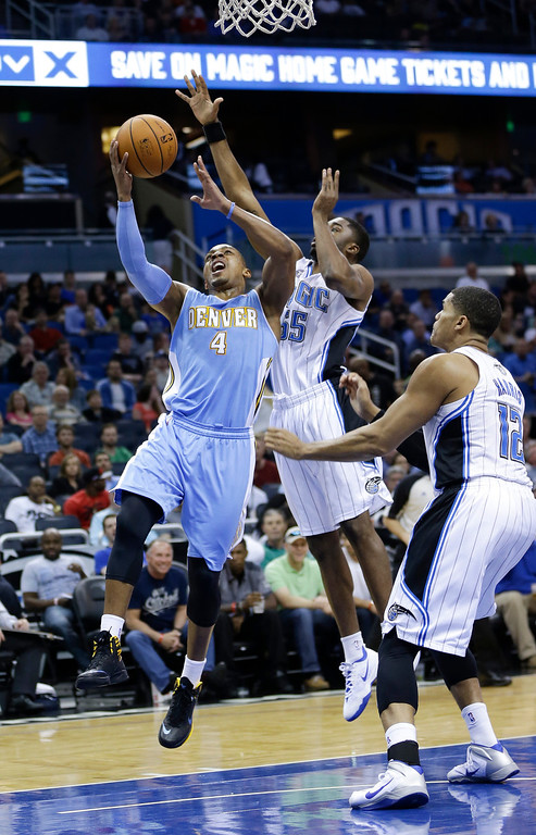 . Denver Nuggets\'s Randy Foye (4) slips past Orlando Magic\'s E\'Twaun Moore, center, and Tobias Harris (12), for a shot during the first half of an NBA basketball game in Orlando, Fla., Wednesday, March 12, 2014. (AP Photo/John Raoux)