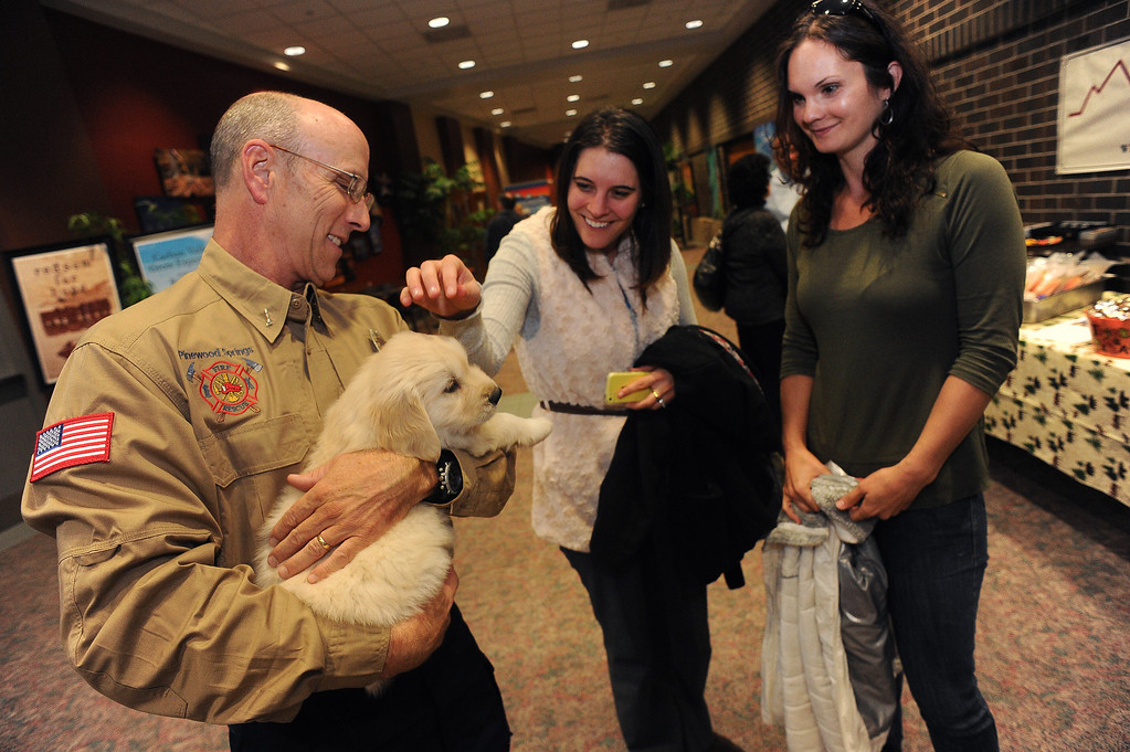 . LONGMONT, CO - OCTOBER 29:   Ted Plank, left, holds 5 week old Chinook as Alyssa Hansen, middle, pets the small puppy at Life Bridge Community Church in Longmont, Co on October 29, 2013. (at right is Melissa Garcia.)  Chinook was born just a few days after the flood.  Her mother was taken out of the Pinewood Springs area via a Chinook helicopter to escape the floods.  Because of this dramatic effort to get the dog to the vet before she gave birth Geri and her husband named this puppy Chinook.  (Photo By Helen H. Richardson/ The Denver Post)