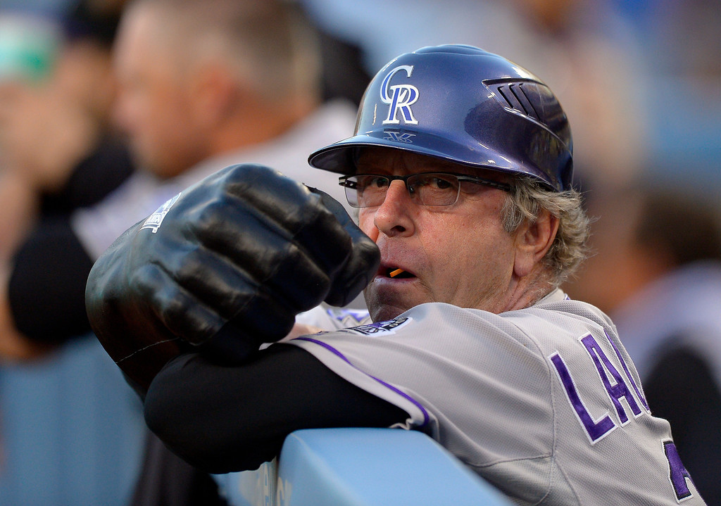 . Colorado Rockies first base coach Rene Lachemann holds a large fist that he uses to fist-pump players before their baseball game against the Los Angeles Dodgers, Wednesday, May 1, 2013, in Los Angeles. (AP Photo/Mark J. Terrill)