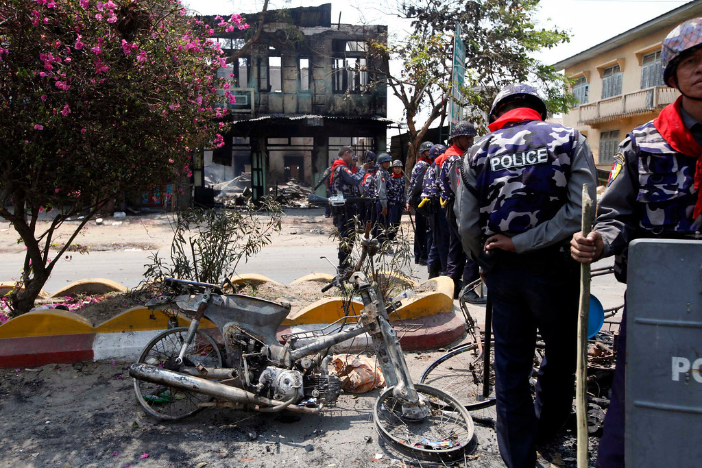 . Myanmar police officers provide security near burnt buildings in Meikhtila, where Ethnic unrest between Buddhists and Muslims continues, in Mandalay division, about 550 kilometers (340 miles) north of Yangon, Myanmar, Friday, March. 22, 2013.  (AP Photo/Khin Maung Win)