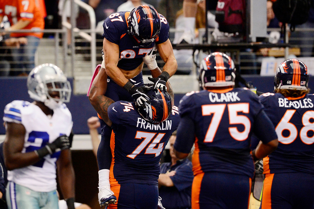 . Orlando Franklin (74) of the Denver Broncos lifts Eric Decker (87) after he caught a touchdown pass against the Dallas Cowboys during the first half of action at AT&T Stadium.   (Photo by AAron Ontiveroz/The Denver Post)