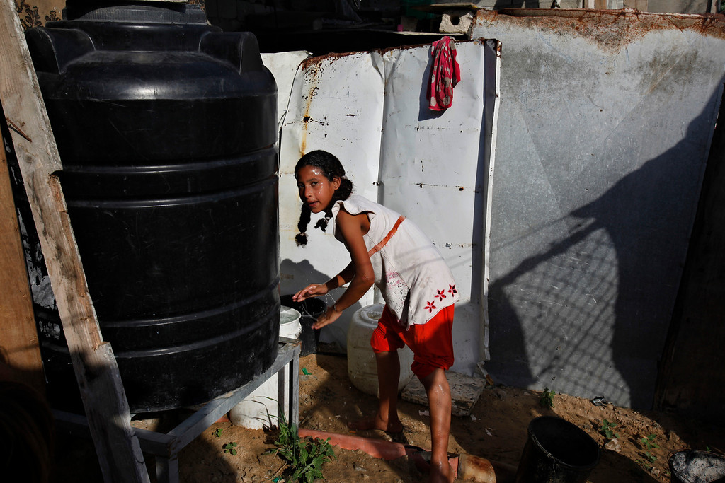 . In this Thursday, Sept. 12, 2013 photo, Manar Alwadiya, 12, washes her face at her family house in Gaza City. The Alwadiya extended family consists of 38 people crowded into small rooms with poor infrastructure. They wash their dishes with water that drips through the roof.  (AP Photo/Adel Hana)