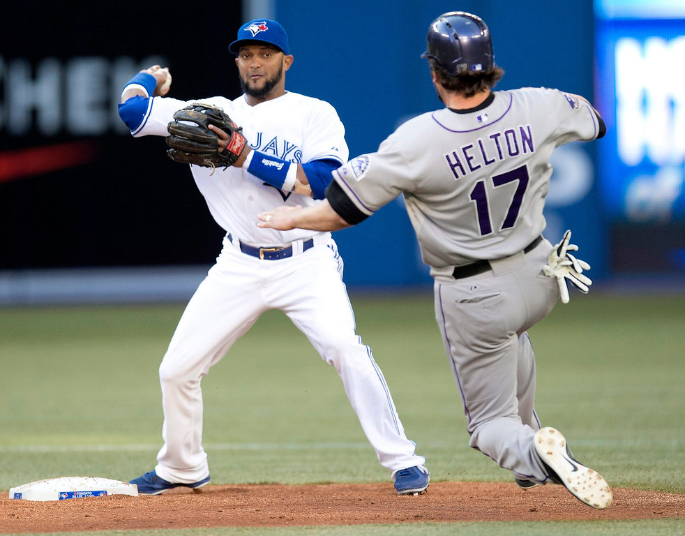 . Toronto Blue Jays\' second baseman Emilio Bonifacio starts his throw to first for the double play as Colorado Rockies\' Todd Helton heads to second during second inning of an inter-league baseball game in Toronto on Tuesday June 18, 2013.   (AP Photo/The Canadian Press, Frank Gunn)
