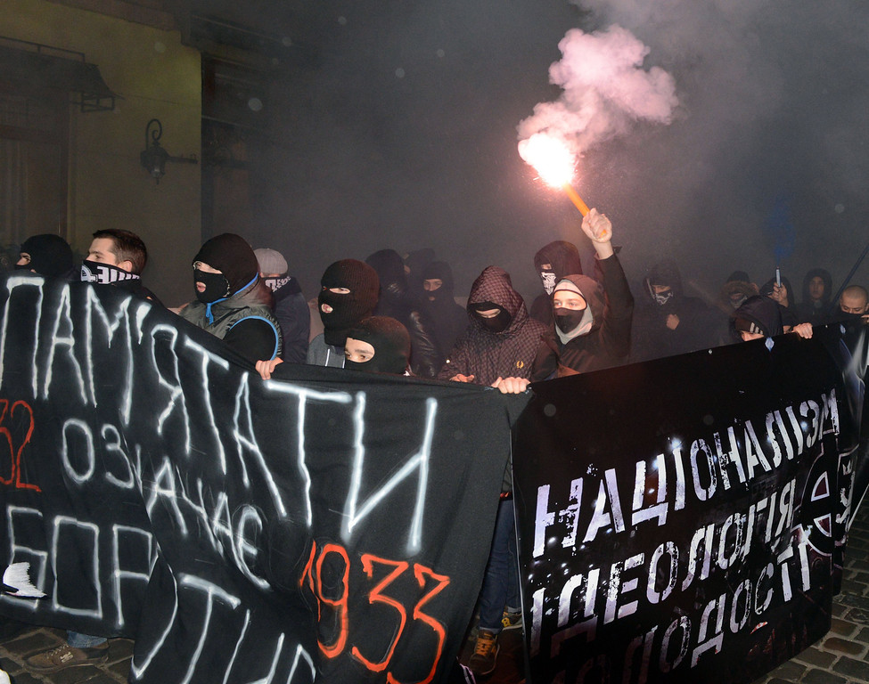 ". Young ultra-nationalists carry placard reading ""1933. Remember - means to fight\"" during their march in memory of the victims of the Holodomor famine in western Ukrainian city of Lviv on November 29, 2013. AFP PHOTO/ YURIY  DYACHYSHYN/AFP/Getty Images"