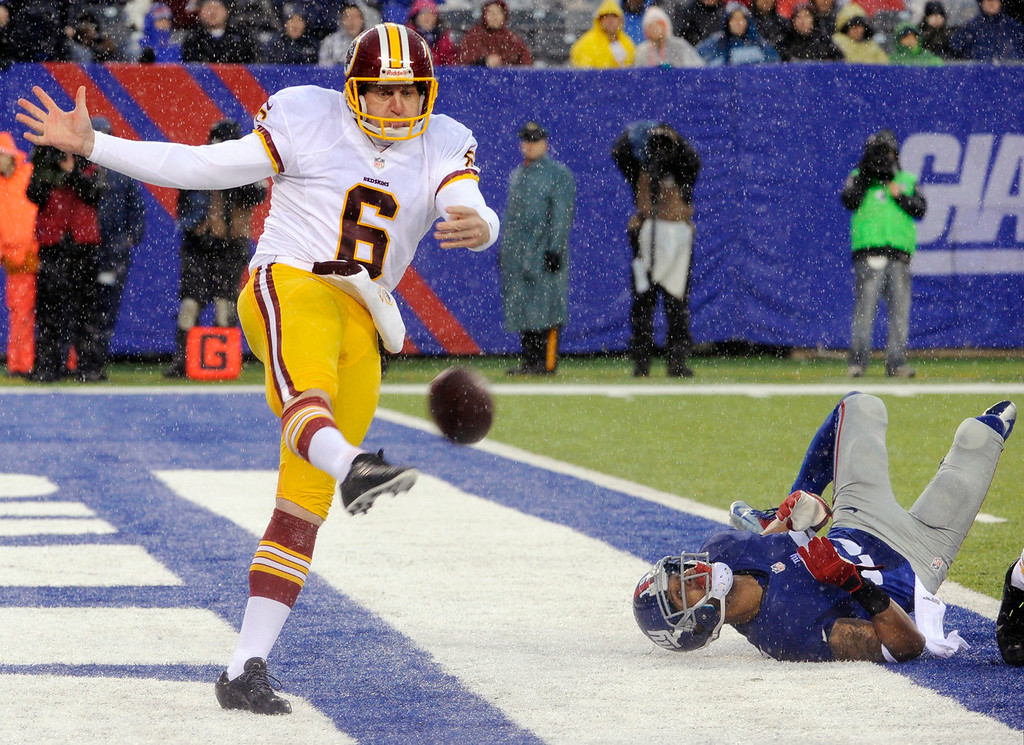 . Washington Redskins punter Sav Rocca (6) kicks the ball away from New York Giants\' Julian Talley (19) during the first half of an NFL football game on Sunday, Dec. 29, 2013, in East Rutherford, N.J. (AP Photo/Bill Kostroun)