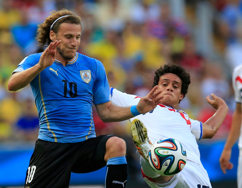 . Uruguay\'s Diego Forlan, left, is challenged by Costa Rica\'s Yeltsin Tejeda during the group D World Cup soccer match between Uruguay and Costa Rica at the Arena Castelao in Fortaleza, Brazil, Saturday, June 14, 2014.(AP Photo/Bernat Armangue)