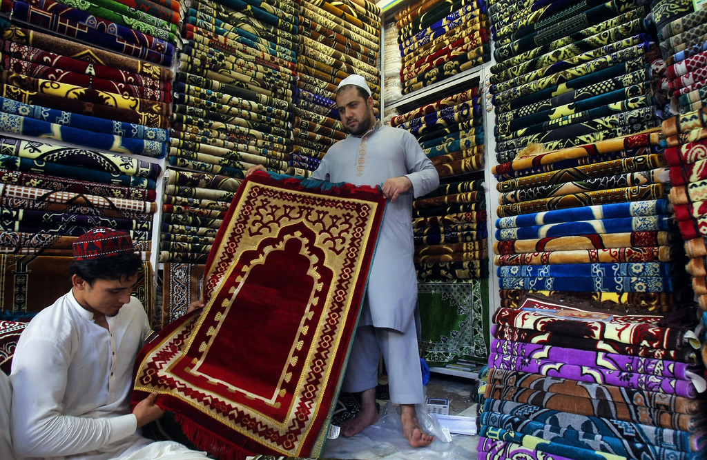 . A Pakistani Muslim buys a praying rug at a shop as he prepares for Islamic holy month of Ramadan in Peshawar, Pakistan, Saturday, July 28, 2014. Muslims throughout the world are preparing to celebrate the holy fasting month of Ramadan, when they refrain from eating, drinking, and smoking from dawn to dusk. Muslims usually increase their religious activities during the Ramadan. (AP Photo/Mohammad Sajjad)