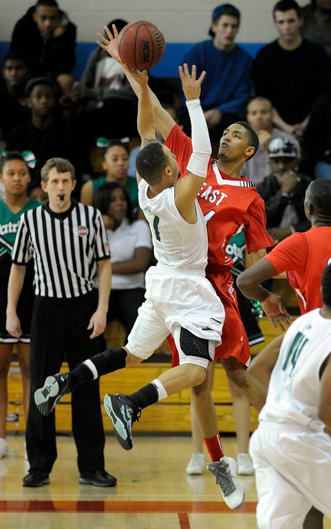 . DENVER, CO. - FEBRUARY 16: East defender Dominique Collier (24) went for the block on GW guard Michael Hudgens (1) in the first quarter. The Denver East High School boy\'s basketball team defeated George Washington 82-20 Saturday afternoon, February 16, 2013.  (Photo By Karl Gehring/The Denver Post)