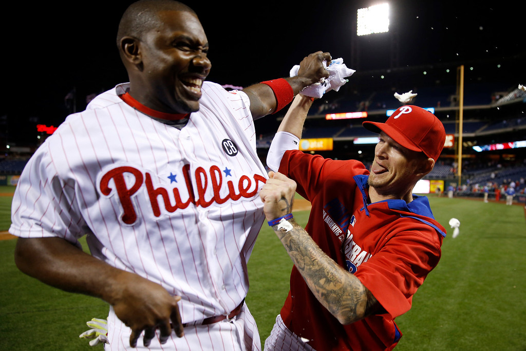 . Philadelphia Phillies\' A.J. Burnett, right, tries to hit Ryan Howard with a towel of shaving cream after Howard\'s game-winning three-run home run during the ninth inning of a baseball game against the Colorado Rockies, Wednesday, May 28, 2014, in Philadelphia. Philadelphia won 6-3. (AP Photo/Matt Slocum)