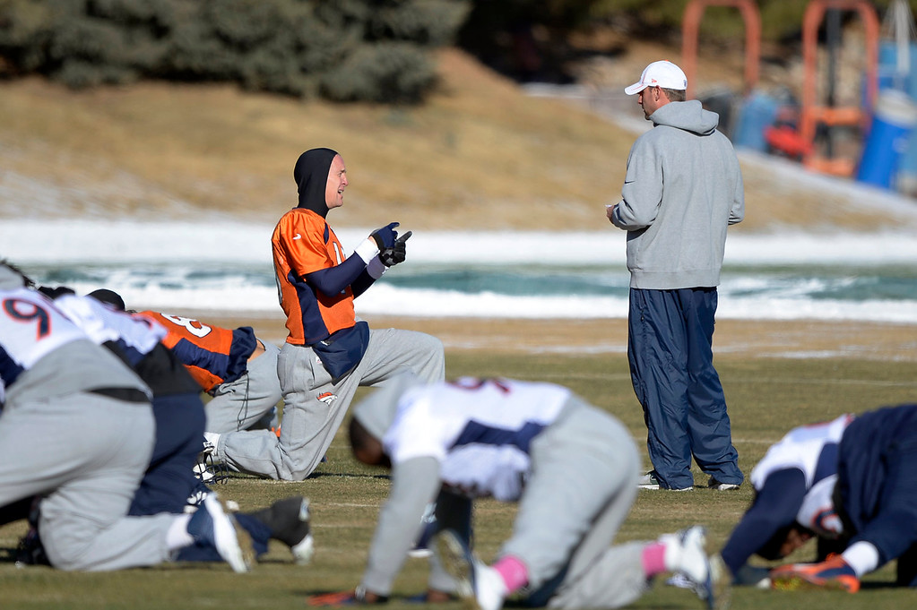 . Denver Broncos quarterback Peyton Manning (18) talks with Adam Gase before practice January 2, 2014 at Dove Valley (Photo by John Leyba/The Denver Post)